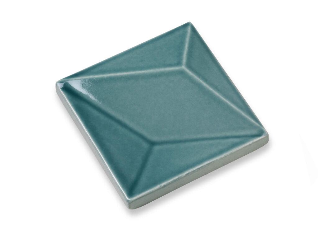 Fliese LUX in der Farbe Petrol. Das Bild zeigt eine einzelne LUX-Fliese in einem tuerkis-blauen Farbton. Die Datei ist ein Foto im JPEG-Format.