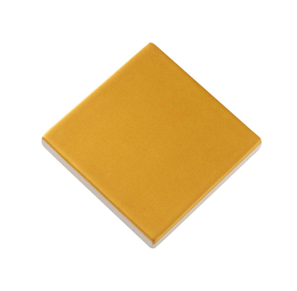Fliese PLAETTLI in der Farbe Amber matt. Das Bild zeigt eine einzelne PLAETTLI-Fliese in einem orange-gelben, matten Farbton. Die Datei ist ein Foto im JPEG-Format.