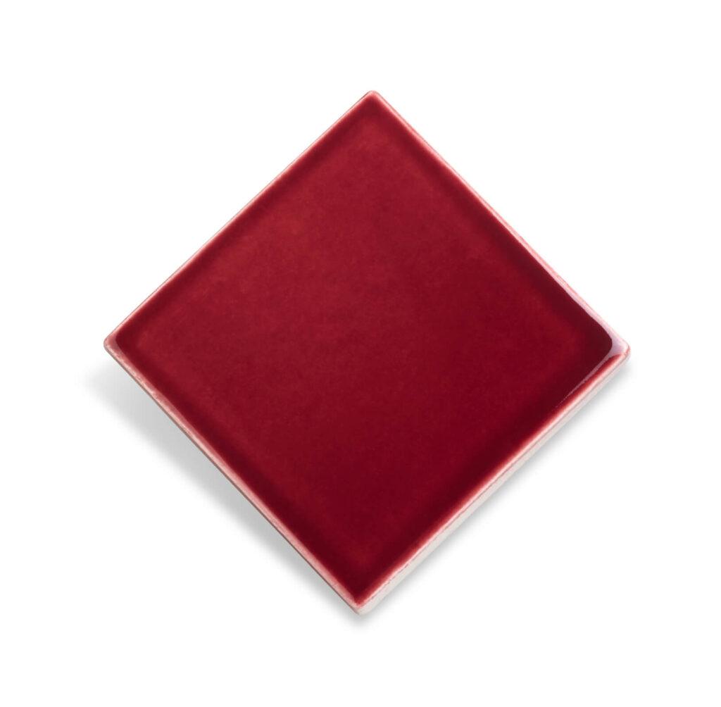 Fliese PLAETTLI in der Farbe Berry. Das Bild zeigt eine einzelne PLAETTLI-Fliese in einem dunkelroten Farbton. Die Datei ist ein Foto im JPEG-Format.