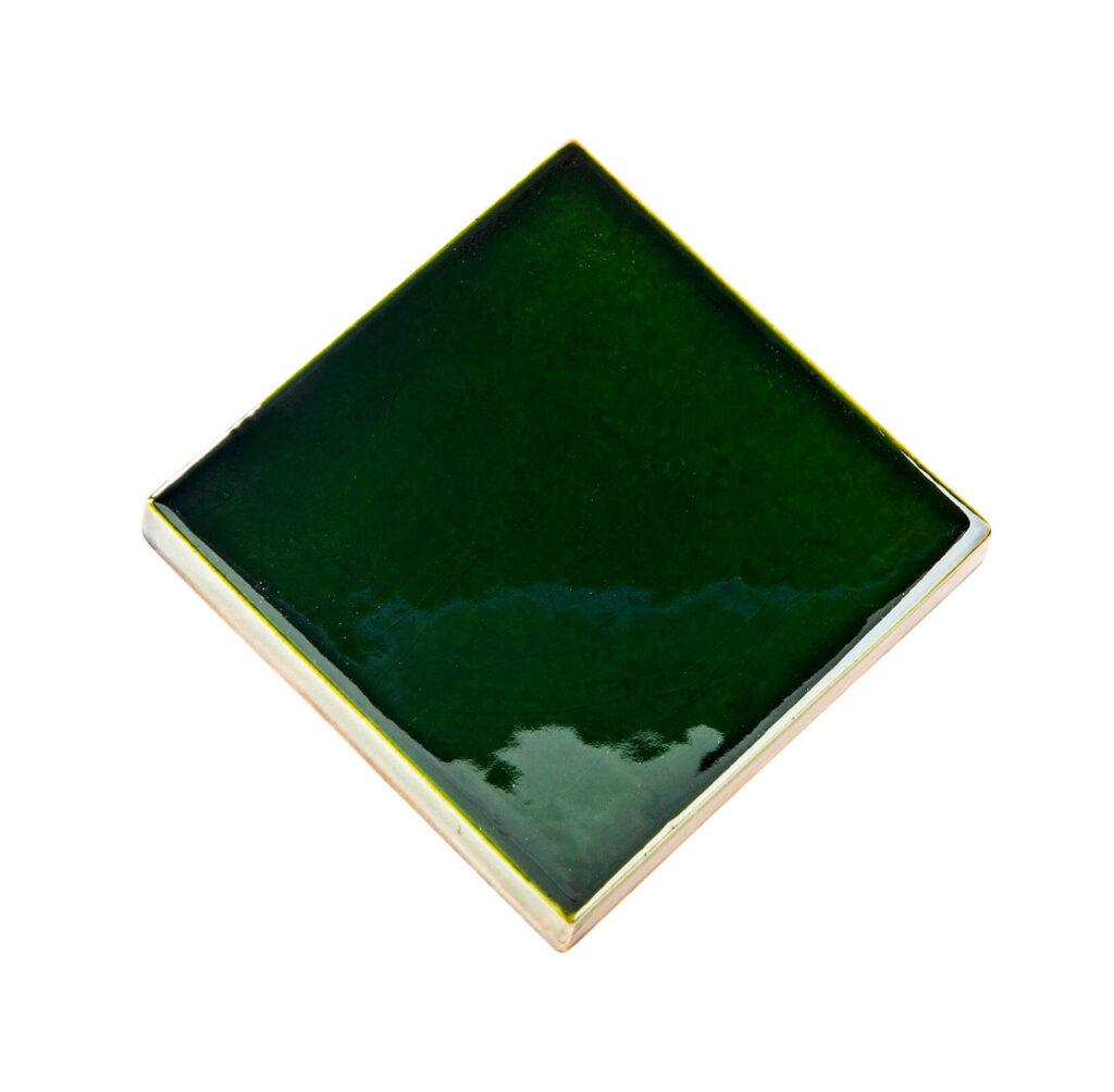 Fliese PLAETTLI in der Farbe Bottle Green. Das Bild zeigt eine einzelne PLAETTLI-Fliese in einem dunkelgruenen Farbton. Die Datei ist ein Foto im JPEG-Format.