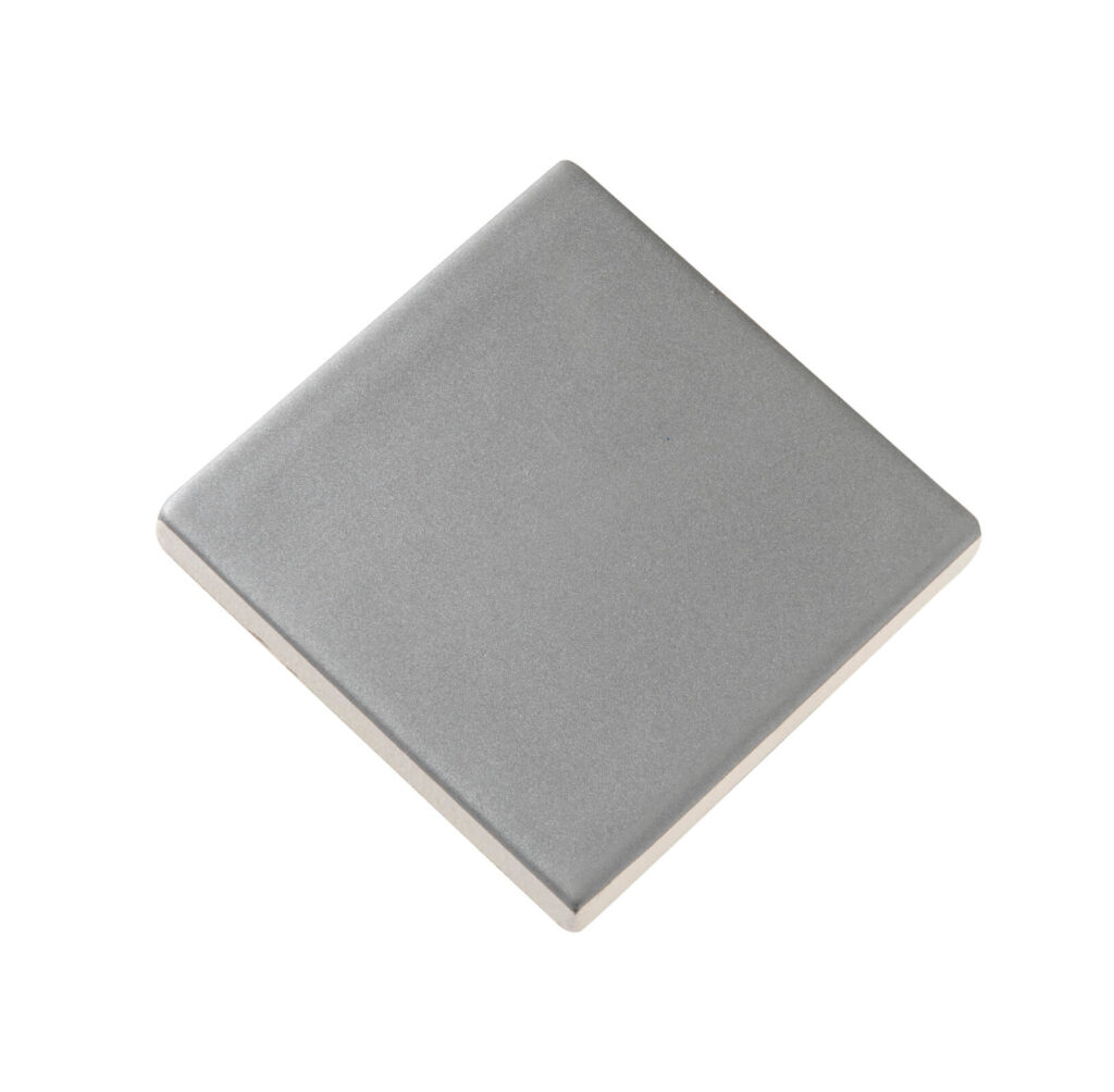 Fliese PLAETTLI in der Farbe Grey matt. Das Bild zeigt eine einzelne PLAETTLI-Fliese in einem grauen, matten Farbton. Die Datei ist ein Foto im JPEG-Format.