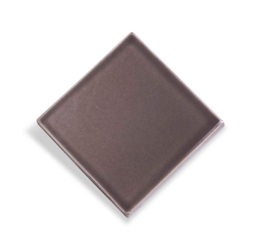 Fliese PLAETTLI in der Farbe Mocca. Das Bild zeigt eine einzelne PLAETTLI-Fliese in einem braunen Farbton. Die Datei ist ein Foto im JPEG-Format.