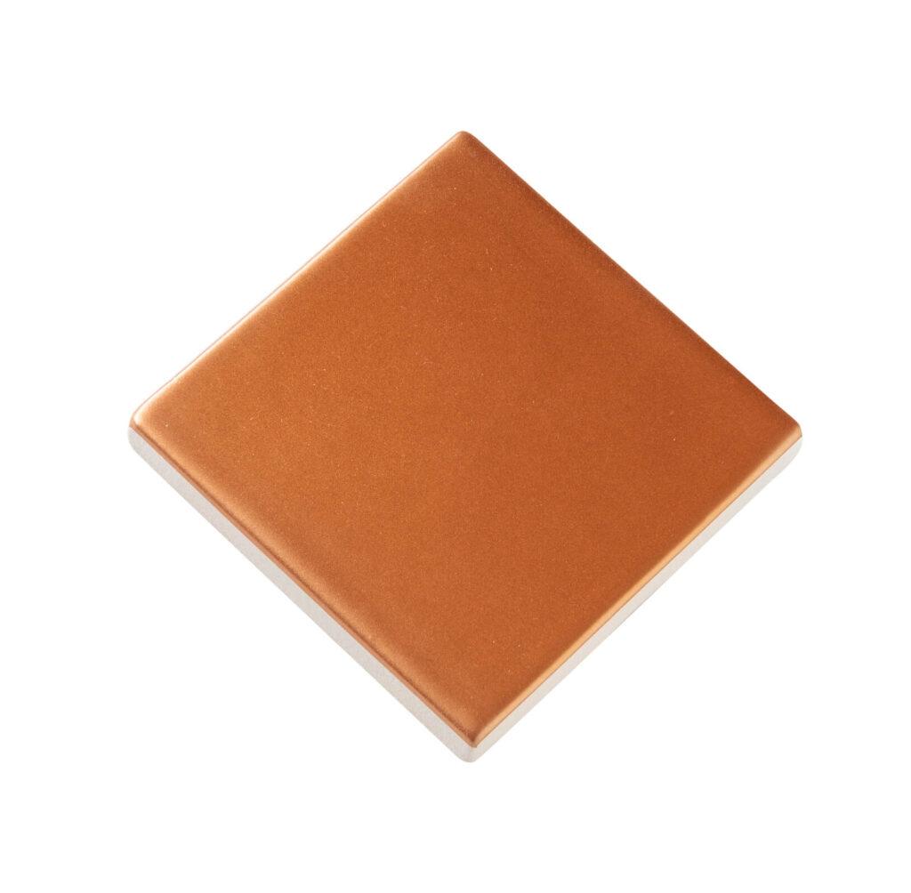 Fliese PLAETTLI in der Farbe Orange. Das Bild zeigt eine einzelne PLAETTLI-Fliese in einem orangenen Farbton. Die Datei ist ein Foto im JPEG-Format.