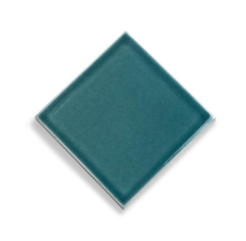 Fliese PLAETTLI in der Farbe Petrol. Das Bild zeigt eine einzelne PLAETTLI-Fliese in einem tuerkis-blauen Farbton. Die Datei ist ein Foto im JPEG-Format.