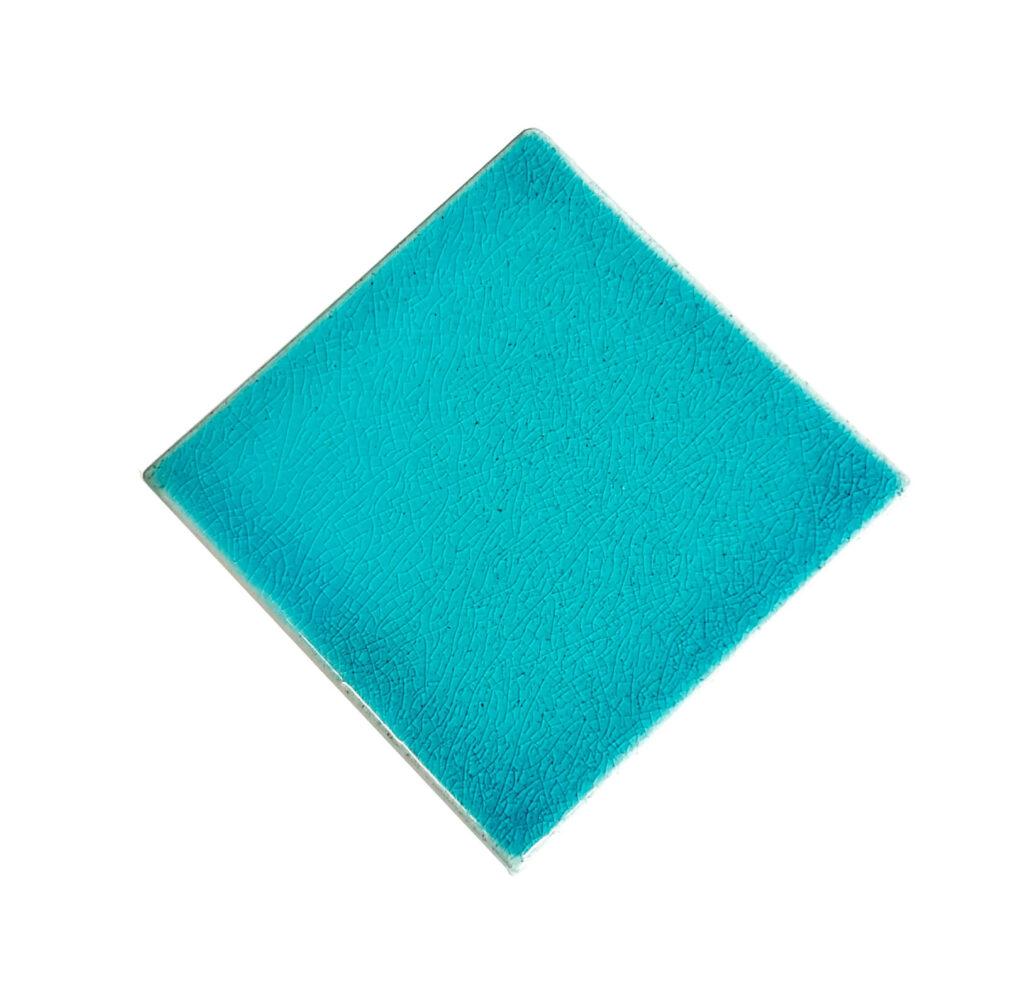 Fliese PLAETTLI in der Farbe Turquoise-craquele. Das Bild zeigt eine einzelne PLAETTLI-Fliese in einem tuerkisen Farbton mit Craquele-Effekt. Die Datei ist ein Foto im JPEG-Format.